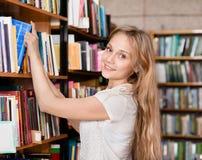 愉快的学生在书包围的图书馆里 免版税图库摄影
