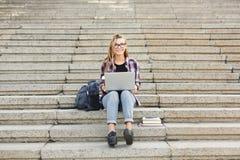 愉快的学生坐台阶使用膝上型计算机 图库摄影