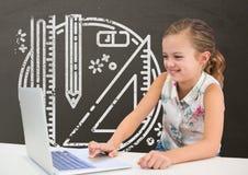 愉快的学生女孩在使用一台计算机的桌上反对有学校和教育图表的灰色黑板 免版税库存图片