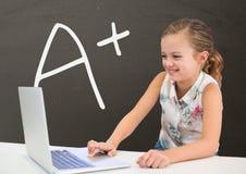 愉快的学生女孩在使用一台计算机的桌上反对有A+文本的灰色黑板 库存图片