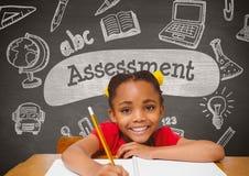 愉快的学生女孩在反对灰色黑板的桌上有评估文本的和教育和学校gr 库存图片