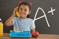 愉快的学生女孩在拿着香蕉的桌上反对有A+文本的灰色黑板 库存图片