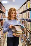 愉快的学生女孩或妇女有书的在图书馆里 免版税图库摄影