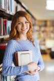 愉快的学生女孩或妇女有书的在图书馆里 库存图片