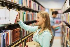 愉快的学生女孩或妇女有书的在图书馆里 免版税库存照片