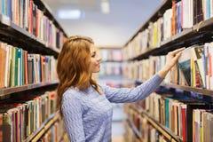愉快的学生女孩或妇女有书的在图书馆里 库存照片