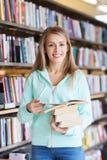 愉快的学生女孩或妇女有书的在图书馆里 免版税库存图片