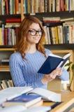愉快的学生女孩阅读书在图书馆里 免版税库存照片