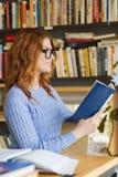 愉快的学生女孩阅读书在图书馆里 库存照片