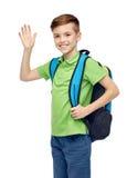 愉快的学生男孩用书包挥动的手 免版税库存照片