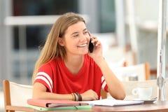 愉快的学生谈话在酒吧的电话 免版税库存照片
