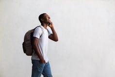 愉快的学生走和谈话在手机 免版税图库摄影