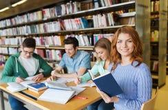愉快的学生阅读书在图书馆里 免版税库存图片