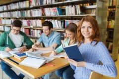 愉快的学生阅读书在图书馆里 免版税图库摄影