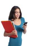 愉快的学生青少年的举行的书和发短信在一个巧妙的电话 库存照片