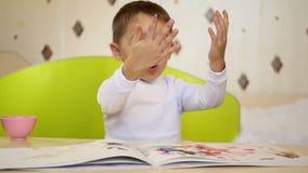 愉快的学龄前孩子参与画的油漆 淘气鬼采取油漆并且拍他的在本文的棕榈 股票录像