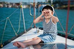 愉快的孩子上尉坐豪华小船有后边海背景 库存图片