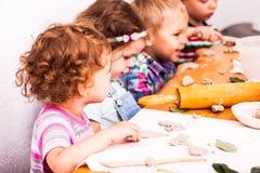 愉快的孩子与雕塑黏土衔接 免版税图库摄影