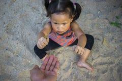 愉快的孩子使用与沙子的,滑稽的亚洲家庭在公园 库存图片