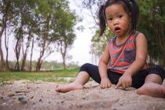 愉快的孩子使用与沙子的,滑稽的亚洲家庭在公园 免版税库存照片