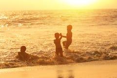愉快的孩子使用在海的小组 免版税库存照片