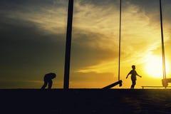 愉快的孩子剪影海滩的与惊人的日出 库存图片