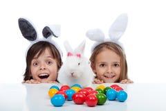 愉快的孩子发现了在白色和蛋死的站点-隔绝的复活节兔子 免版税图库摄影