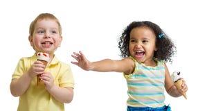 愉快的孩子吃冰淇凌的男孩和女孩被隔绝 免版税图库摄影