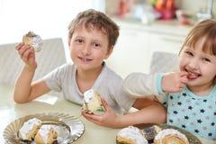 愉快的孩子吃酥皮点心在明亮的厨房里在桌上 图库摄影