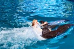愉快的孩子和海豚在大海 免版税图库摄影