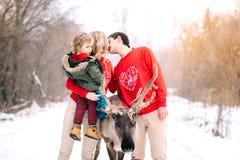 愉快的孩子和父母在冬天户外 一个快乐的家庭的画象与鹿的 免版税库存照片