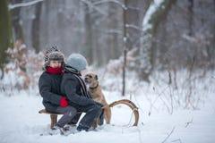 愉快的孩子在一个冬天停放,使用与爬犁一起 免版税库存图片