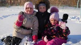 愉快的孩子在冬天公园拥抱自己和微笑 股票录像