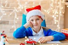 愉快的孩子在圣诞节的圣诞老人盖帽 免版税库存图片