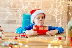 愉快的孩子在圣诞节的圣诞老人盖帽 图库摄影