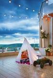 愉快的孩子在手工制造圆锥形小屋掩藏从突然的夏天雨在露台,一起使用 库存图片