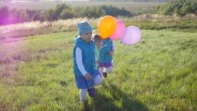 愉快的孩子在有气球的公园跑握手 股票视频