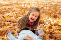 愉快的孩子在秋天停放说谎在叶子 免版税图库摄影