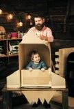 愉快的孩子在纸板手工制造火箭坐 父母身分概念 与爸爸,父亲的男孩戏剧,小宇航员参加  免版税库存照片