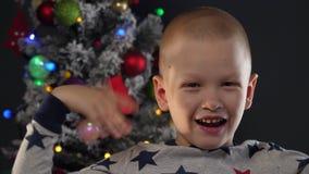 愉快的孩子在诗歌选和绿色飞碟火球,发光的球形,闪光灯显示在圣诞树前面的鬼脸 股票视频