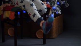 愉快的孩子在诗歌选和绿色飞碟火球,发光的球形,闪光灯显示在圣诞树前面的鬼脸 影视素材