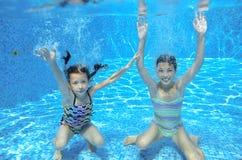 愉快的孩子在水池游泳在水面下,女孩游泳 免版税图库摄影