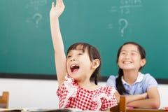 愉快的孩子在类的被举的手 免版税库存照片