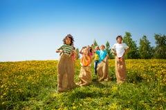 愉快的孩子在绿色草甸的大袋跳 免版税库存照片
