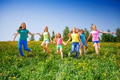 愉快的孩子在绿色草甸跑并且握手 库存照片
