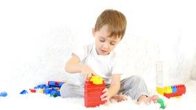 愉快的孩子坐长沙发,使用在色的块,坐白色背景 股票录像