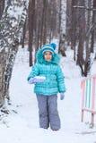 愉快的孩子女孩孩子户外在冬天开掘的雪 库存照片