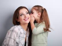 愉快的孩子女孩耳语秘密对她ea的微笑的母亲 免版税库存图片