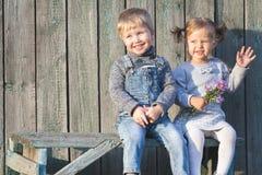 愉快的孩子室外在秋季,坐在长凳 第一个日期 免版税库存图片