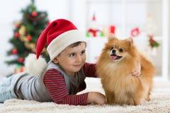 愉快的孩子小男孩和狗作为他们的礼物在圣诞节 圣诞节内部 免版税库存照片